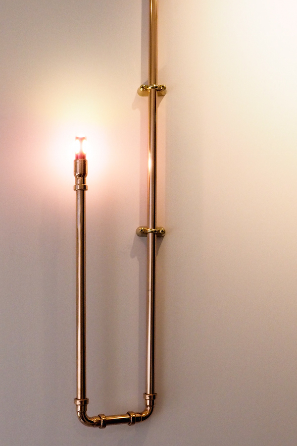 pale pink walls from little greene paints are illuminated by dog's body copper piping as a candelabra