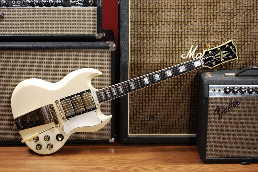 A Gibson SG next to a pile of amplifiers.