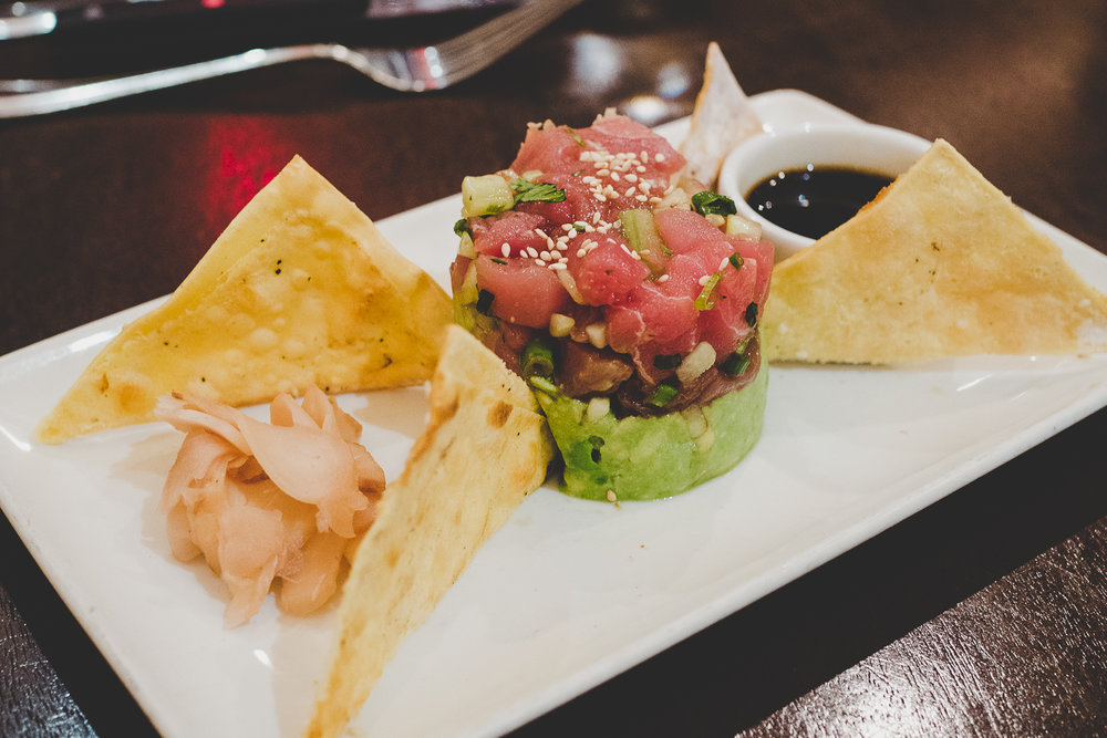 Ahi Tuna Tartare.  Fresh ahi tuna with avocado, cucumber, sesame wonton chips, and a soy reduction.