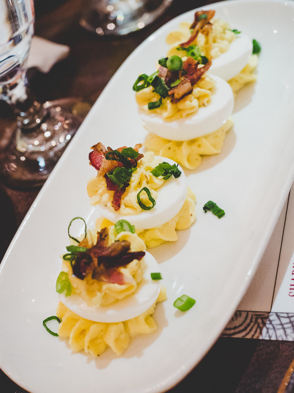 Deviled Eggs.  Four sinfully good eggs topped with maple-Cajun bacon.