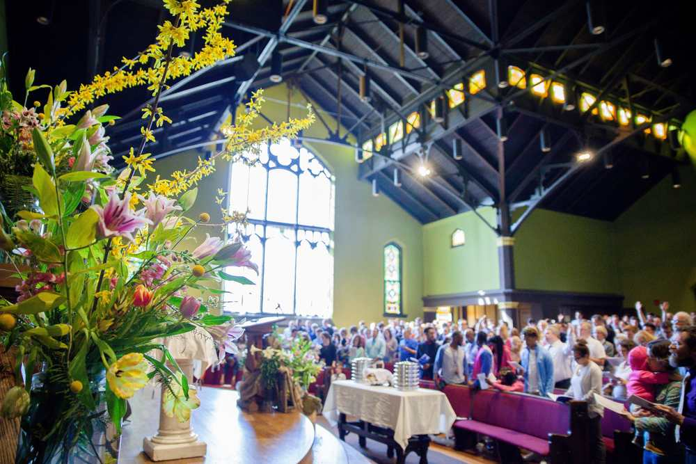 Above: Our sanctuary decorated with Easter flowers and set up for communion. Our sanctuary is often decorated with art installations created by artists in our community and congregation. Photo Credit: Mark Wikkerink