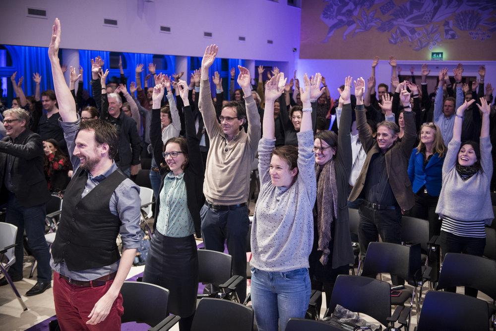 Hogeschool van amsterdam - 07 november 2017 - Nee, hier juicht het publiek nog niet voor de winnaar van de HvA Research Awards 2017. Ze zijn aan het dansen.Want ook dit nietsvermoedende publiek hadden we binnen no-time aan het dansen, inclusief een grote lach op het gezicht!fotograaf:Bram Budel