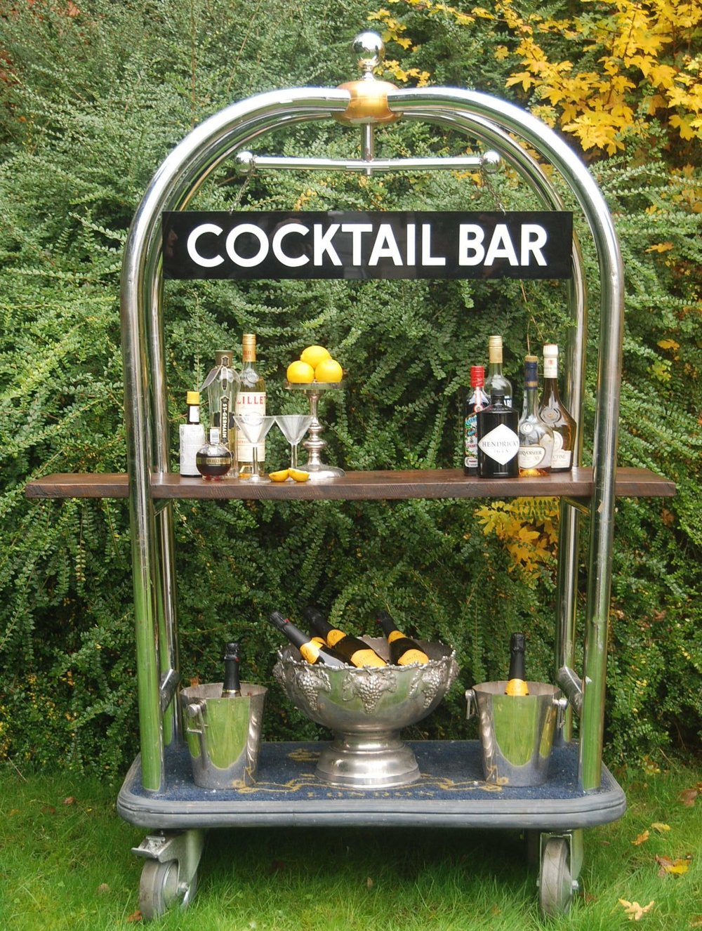 Ritz Trolley Luggage Cocktail Bar Set - includes: Ritz luggage trolley, 1950s cocktail bar sign, two copper champagne buckets, one champagne bowl, wire bottle holder and cocktail shaker - £100