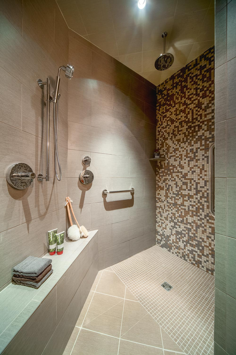 - This shower has a through-the-ceiling rain shower head, as well as grab bars, a seat, and a handheld shower head.