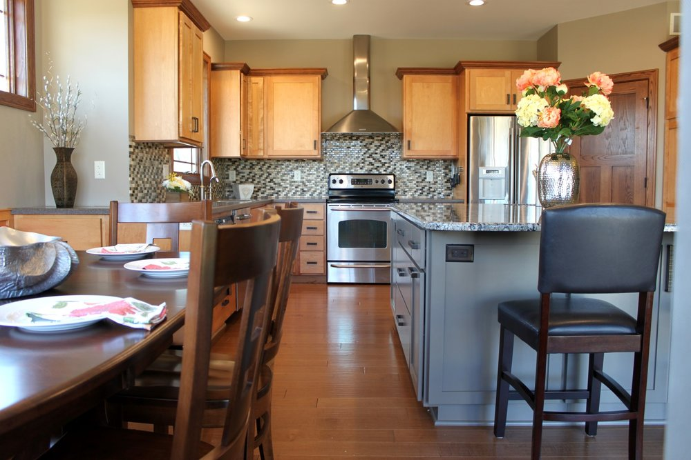 - A tumbled stone mosaic backsplash tile complements the grey tones of the countertops and the warm stained wood.