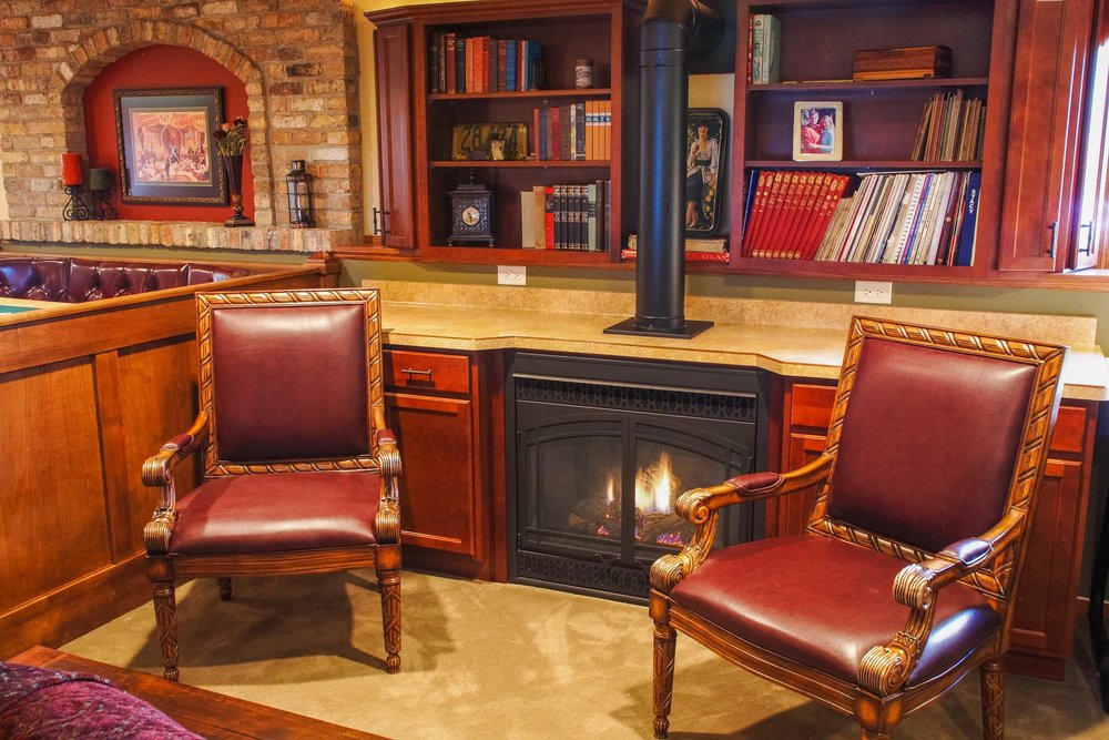 a finished basement is a great place to let your creativity and personality show. this fireplace is built into cabinetry in a non-typical fashion, for design flair and functional comfort. the bookshelves, reclaimed chicago brick, and game table are just a few of the personal touches in this lower level.