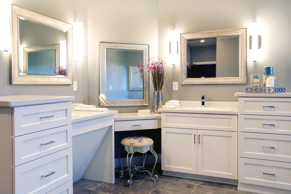 ONE VANITY IS TRADITIONAL, WHILE THE OTHER HAS AN ANGLED BASE TO CONCEAL PLUMBING PIPES WHILE ALLOWING FOR ACCESSIBILITY. IT IS ALSO IMPORTANT TO CONSIDER THE ELEVATION OF MIRRORS FOR EACH USER OF THE BATHROOM.