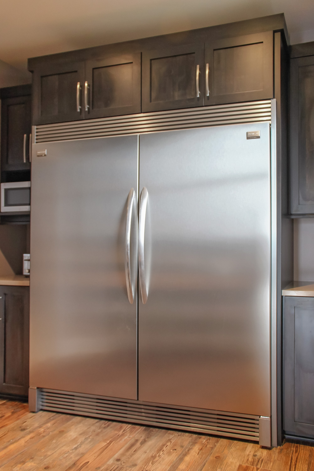 this professional grade refrigerator and freezer combo was placed in the pantry. the kitchen design remains clean, and the pantry also contains a micorwave and countertop space for ease of use.