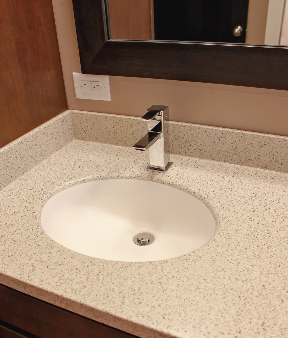 this CHILDREN'S bathroom uses a seamless corian countertop with integral bowl for easy cleaning. the faucet with has single mounting point that balances style, price, and cleaning compared to wall-mounted or widespread faucets with the valves off to each side.