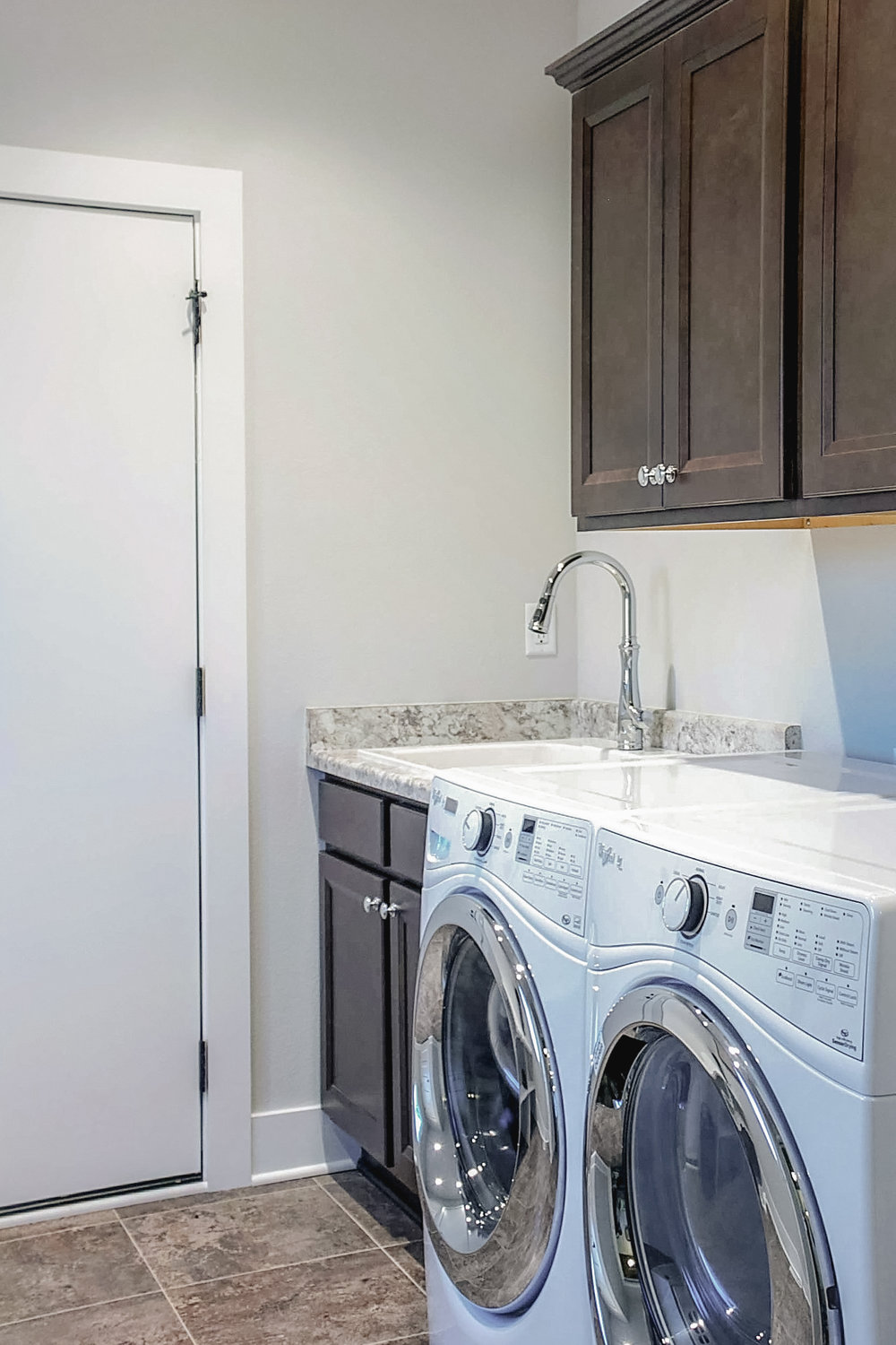 Small Space Laundry Design - The washer, dryer, and a slop sink all fit within about 8 ft in this compact laundry space. Even important storage cabinetry is provided above the washer and dryer, and the two machines held close together provide a flat surface area in lieu of extra countertop.