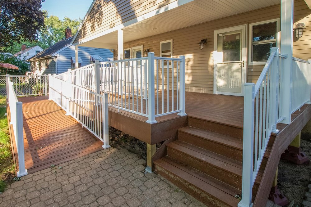 A covered back porch provides a comfortalble outdoor space integrated with the ramp in this aging-in-place remodel.