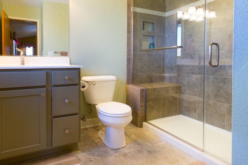 - This remodeled bathroom integrates a LVT bathroom floor with ceramic tile shower walls.
