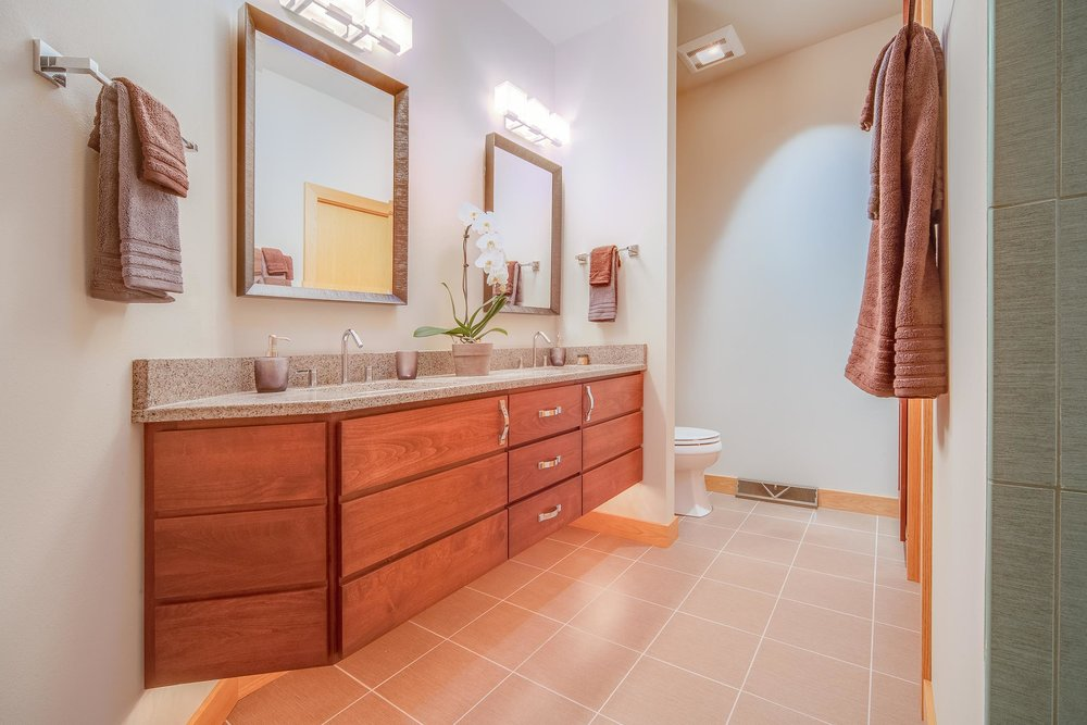 - A wall-mounted floating master bathroom vanity with night lighting underneath.