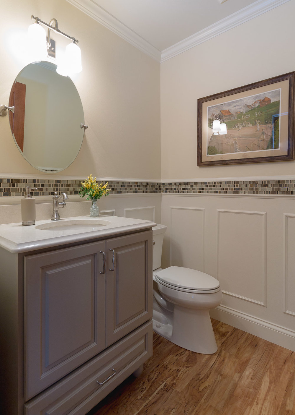 this free standing,furniture style powder room vanity has bun feet and integrates with wainscot design.