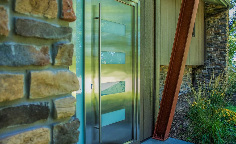 - This stunning stainless steel door is an amazing entry to this transformed contemporary home, but the truth is it was a nightmare to source and install.
