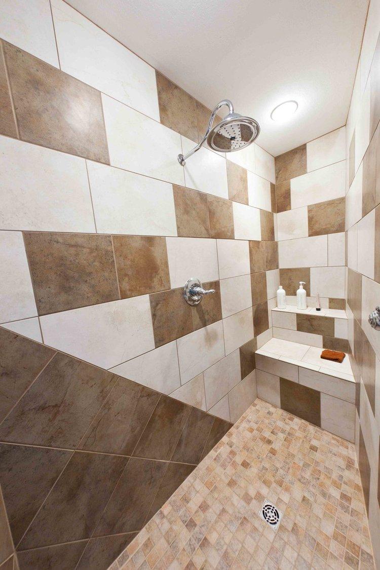 This shower has a wall-mounted rain shower head and unique geometric tile design.