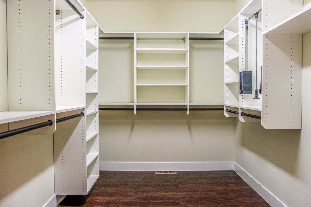 this walk-in closet was created with universal design features in mind. it has hanging and shelves both high and low, and has pull-down racks to easily reach upper hanging clothing.