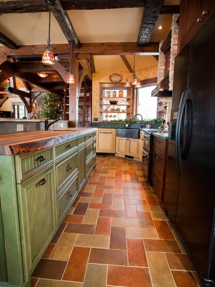 Our clients created a very eclectic kitchen using 3 different cabinet colors, a live-edge wood countertop, and timber framing. green painted cabinets are used on the island.
