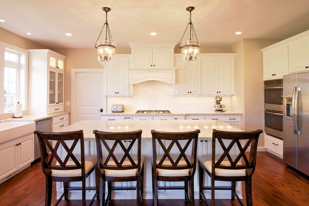 "this large kitchen has a modified ""u"" shape. note that the ""u"" is interrupted at both corners, leaving no wasted corner cabinet space. an island completes the space."