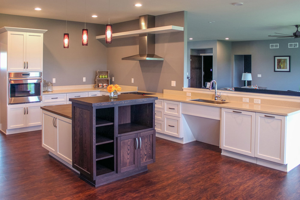 this universal design kitchen includes multiple height work areas, minimal upper cabinets, a roll-under sinnk, and a wall oven.