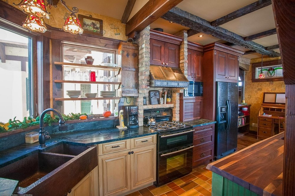 A hammered copper kitchen sink was installed in this one-of-a-kind storybook lake house kitchen.