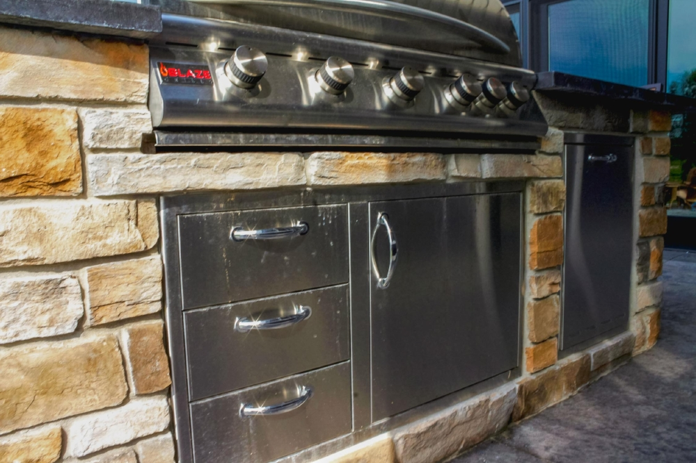 Summer Kitchen Appliances - This outdoor kitchen boasts a refrigerator, grill, and dedicated storage cabinetry. Stainless steel prevents rust.