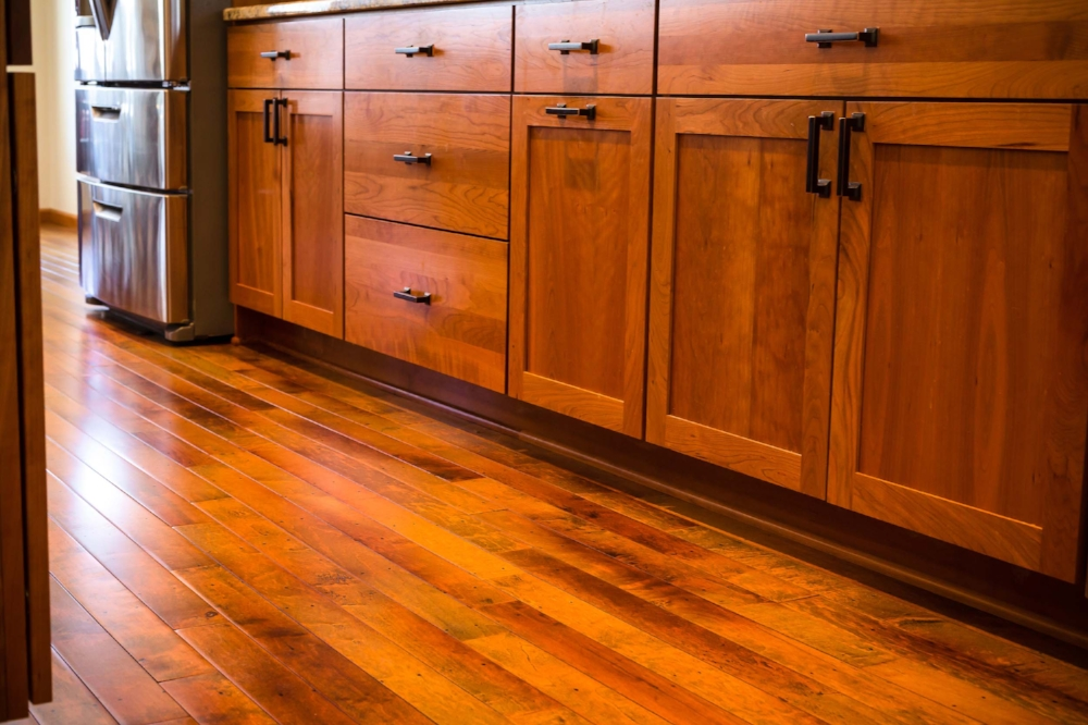 Square Cabinet Hardware - The hardware choice needs to integrate with the overall design style of the kitchen. The rustic wood floor with nail marks ties in to the dark, square edged hardware and the high-contrast wood grain of this remodeled kitchen in Cottage Grove, Wisconsin.