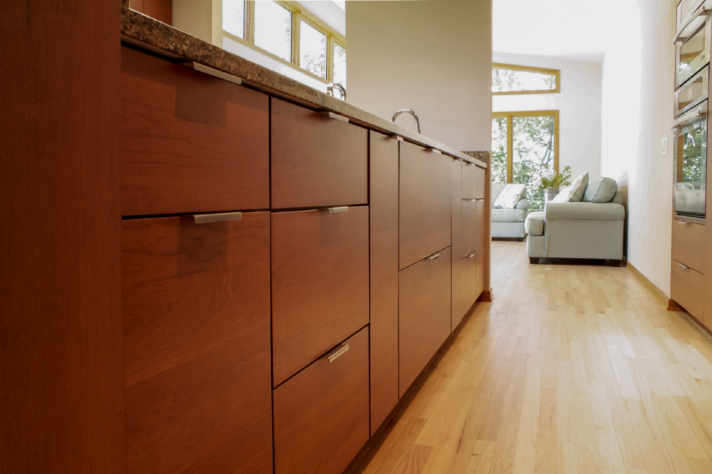 Modern Cabinet Hardware - The brushed chrome finish on this contemporary, minimalist hardware fits in with the contemporary, full-overlay slab cabinet doors in this modern Westport, Waunakee, Wisconsin home.