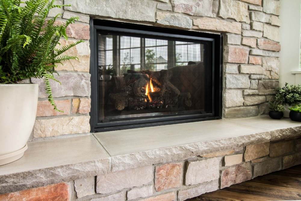 Clean View Gas Log Fireplace - Stone masonry fits tight to the firebox with minimal black metal showing at the edges in a gas log fireplace with a clean view kit. The hearth of a gas fireplace is for decoration and is not required.