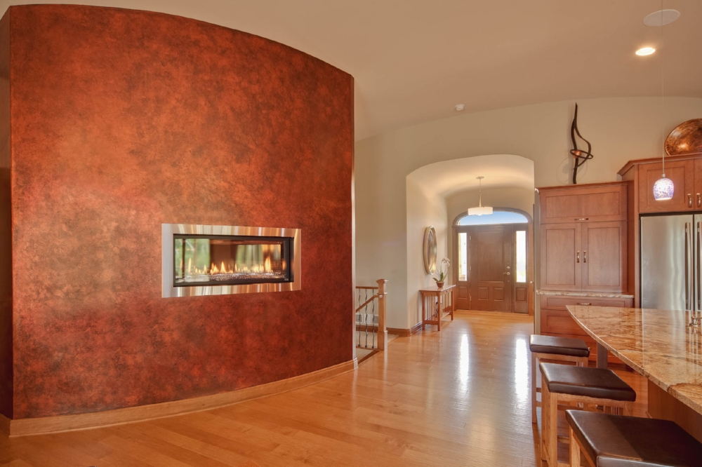 Contemporary Linear Burner Fireplace - Gas fireplaces offer the flexiblity to be installed in modern and non-traditional manners. This linear burner glass fireplace has a curved brushed nickel face, and is installed in a copper metallic decorative painted wall.