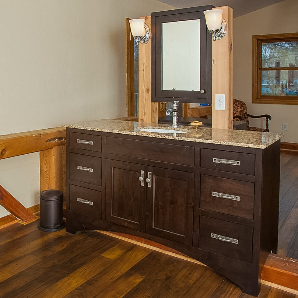 Freestanding Vanity - This vanity was inspired by very traditional elements in the timber-framed home. Inset doors and iron pulls are distinctly rustic elements. Yet the slab drawer panels present a surprisingly sleek contrast, making this vanity a beautiful and unique element.