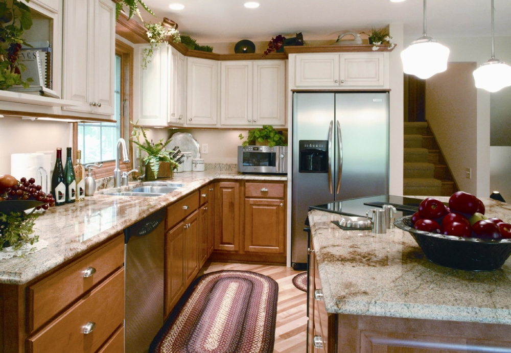 Two-Tone Cabinet Design - This kitchen remodel uses two-tone cabinet design, with the stained crown moulding capping the upper cabinets in the same color as the base cabinets. The glazed painted upper cabinets perfectly compliment the  coloring of the granite countertops.