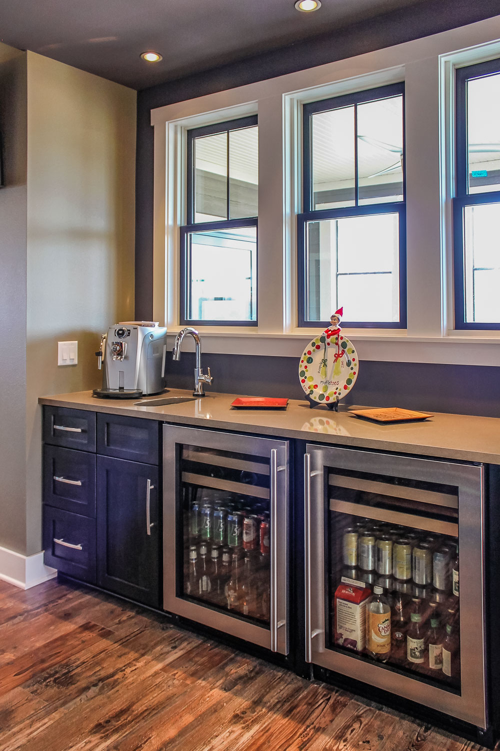 - This butlers pantry area includes an espresso maker, sink, and dual under counter beverage refrigerators.