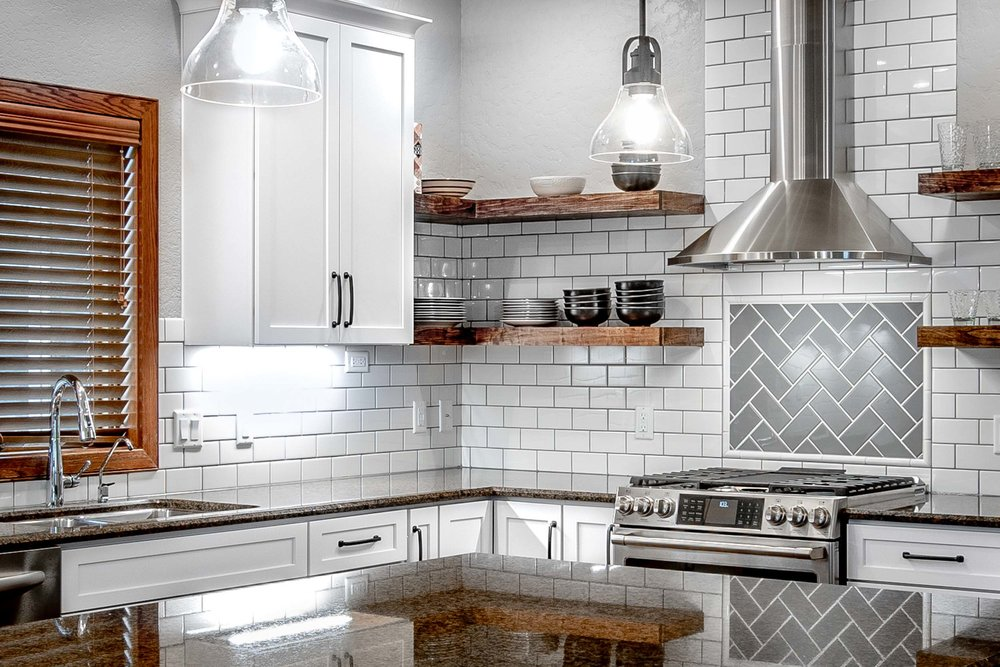 """- The grout in this kitchen was designed to contrast. Note that the white field tile uses dark grout to make it """"pop"""" and that the grey tile behind the range uses white grout to also """"pop"""". Furthermore, the dark grout is the color of the grey tile, and the light grout is the color of the white tile."""