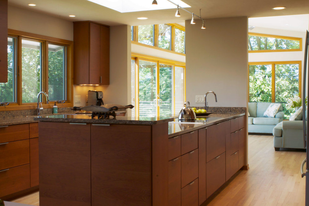 - A creative solution to take advantage of views: The central island is anchored to a piece of wall. Both the main sink and cooktop have optimal views out the large windows. At right, just off the photo, is the set of pantry cabinets, refrigerator, and oven.