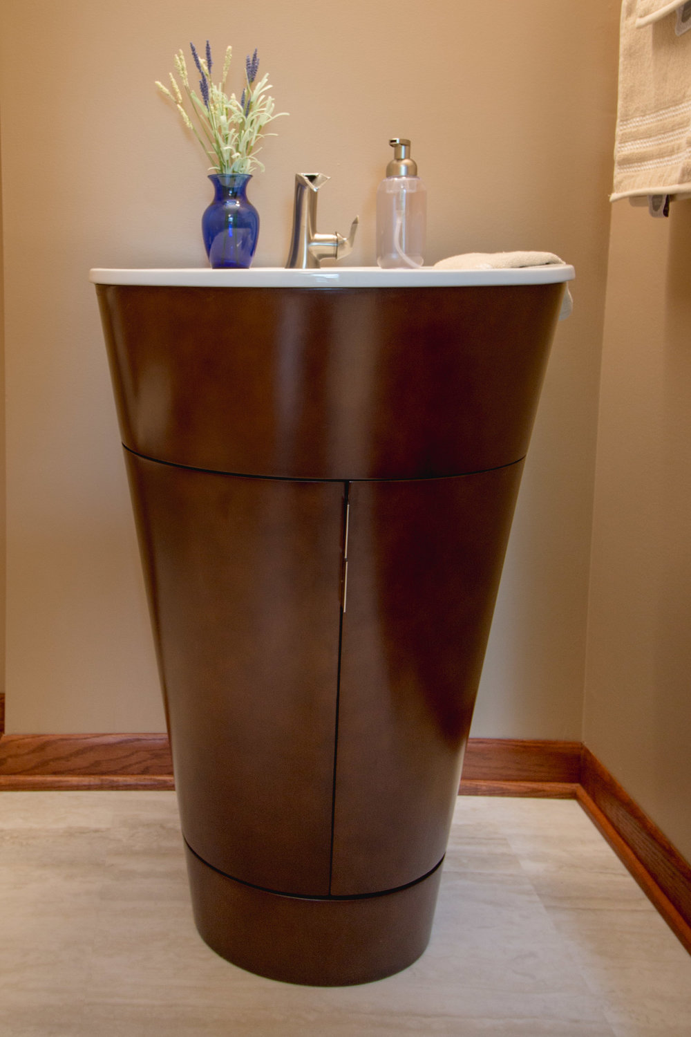 - This pre-manufactured vanity is about the size of a pedestal sink, but provides storage and a sense of elegant whimsy in its shape.