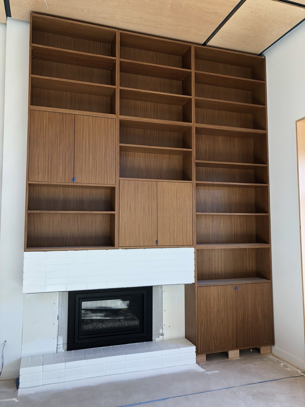 beautiful bookcase in afromosia veneer by Laak Woodworks and a white painted fireplace