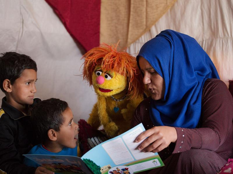 Tonton, a Muppet from  Hikayat Simsim,  Jordan's local version of  Sesame Street , reads a storybook with a refugee family in Lebanon. SOURCE:  TARA TODRAS-WHITEHILL/IRC