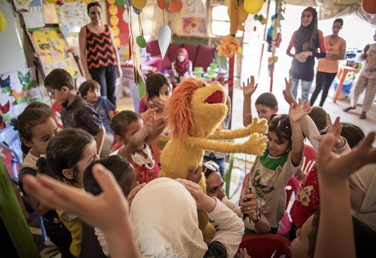 Syrian children living in Bekaa, Lebanon, are excited to receive a surprise visit from Tonton. SOURCE:  JACOB RUSSELL/IRC