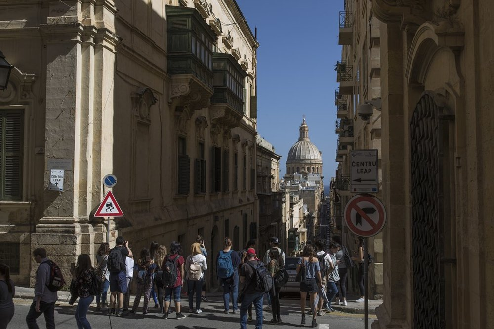 Tourists take photographs down a street on March 11, 2018, in Malta's capital, Valletta.SOURCE  DAN KITWOOD/GETTY