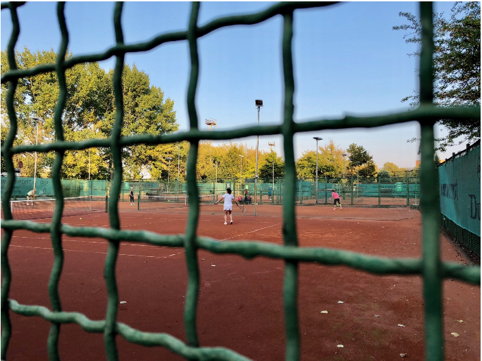 A fenced in section of the Tennis Club SV Berliner Brauereien e.V. The club's seven outdoor courts are located in the Volkspark, or the 'People's Park', which evolved from a World War II dumping ground. The park is just around the corner from a statue of Ernst Thälmann, a leading figure of Weimar Germany's Communist party (KPD) killed in the Buchenwald concentration camp.