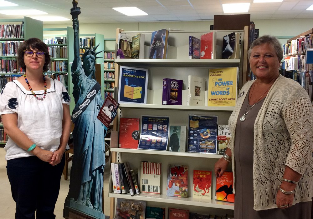 Librarian Charle Ricci (left) and Connie Campbell, Vice President, BB&T, review books on the new book display shelf that the BB&T Lighthouse Project sponsored.