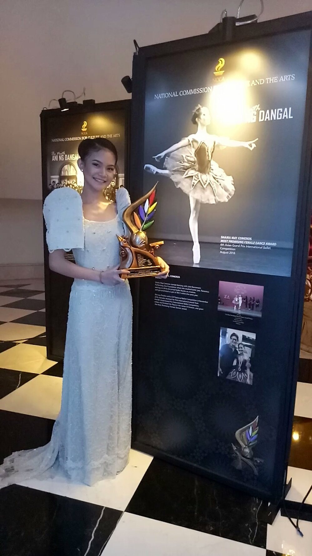 Carrying her Sarimanok trophy, Shaira Comeros stands beside a panel showcasing her achievements in dance.