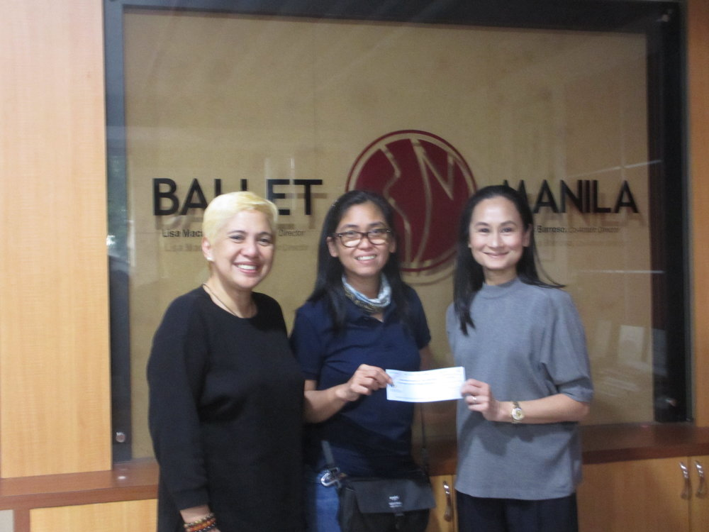 On behalf of PBF, Ballet Manila artistic director Lisa Macuja-Elizalde (right) receives from photographer G-nie Arambulo a check representing proceeds from her exhibit that she collaborated on with writer Angela Ureta (left).