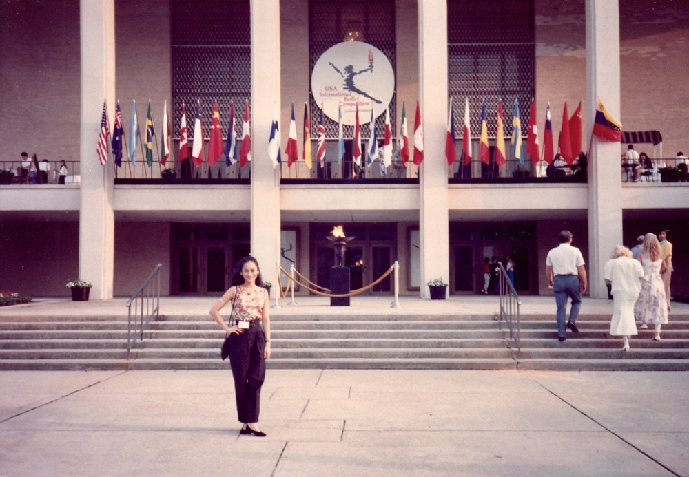 "Lisa poses in front of the competition venue where flags of participating countries were displayed throughout the event held from June 17 to July 1, 1990. Known as the ""Olympics of Ballet"", the USA IBC – similar to the sports showcase – is held every four years and, for its opening ceremonies, features a lighting of the flame and a parade of nations."