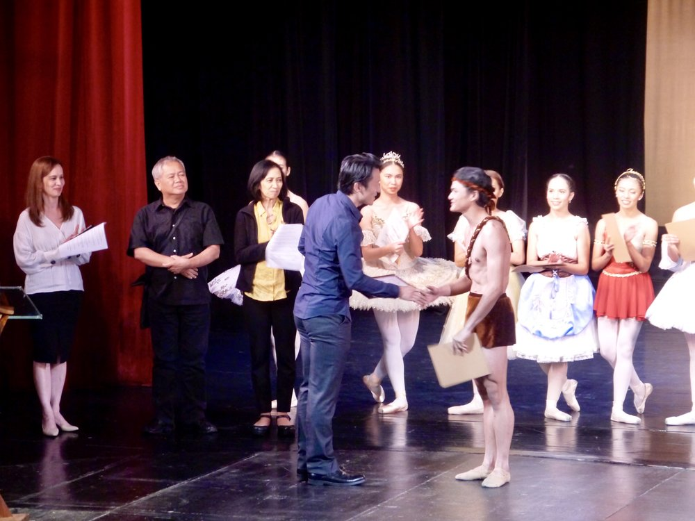 Joshua Enciso receives his award from juror Qi Huan as jurors Melanie Motus, Raul Sauz and Myra Beltran and senior competitors look on.