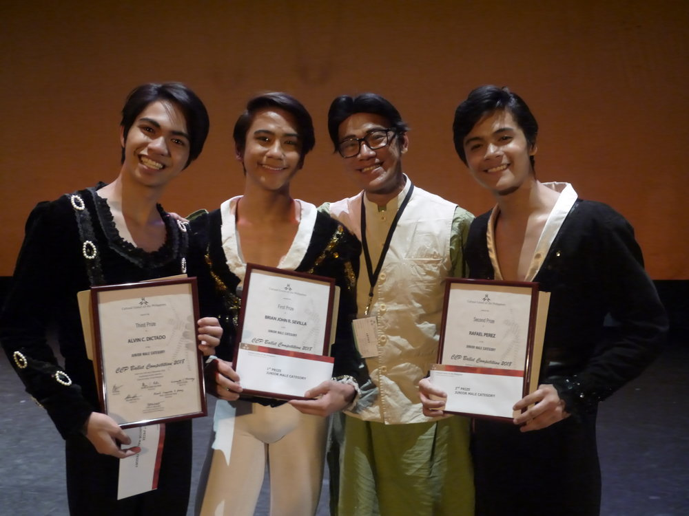 Ballet Manila co-artistic director Osias Barroso congratulates winning junior danseurs in the CCP Ballet Competition: (from left) Alvin Dictado, third prize; Brian Sevilla, first prize; and Rafael Perez, second prize. Photo by Giselle P. Kasilag