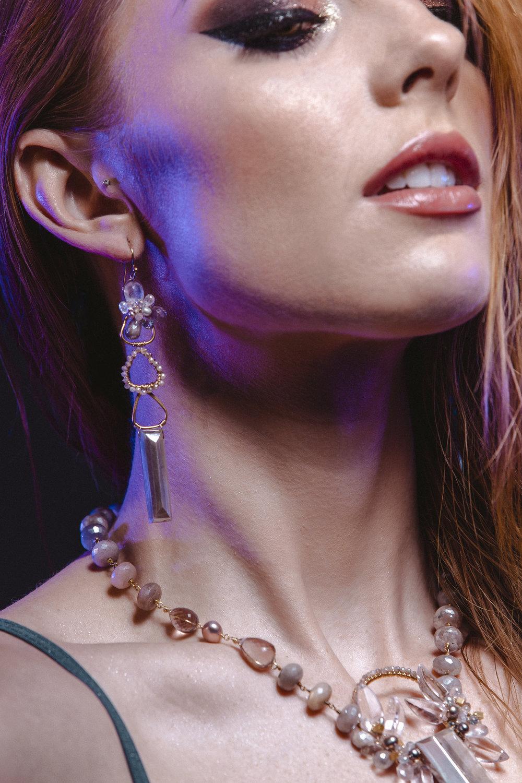 Model wearing long pendant gemstone earrings