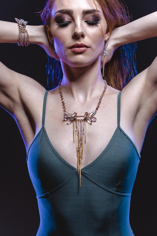 Model wearing long spike pendant gemstone earring
