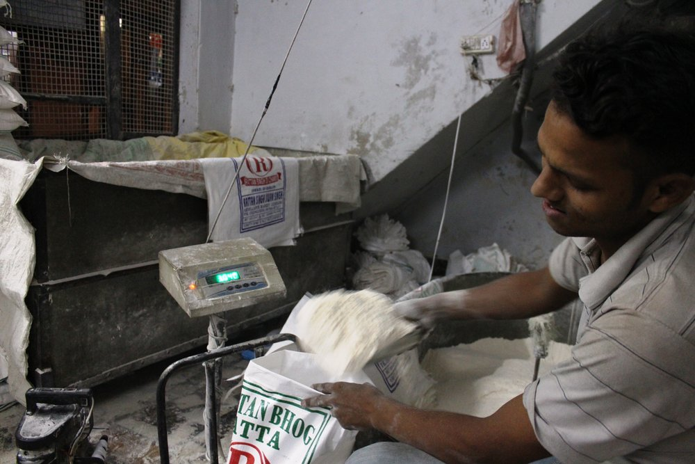 Mill worker weighing and packing a bag of flour before dispatching it to customers, 23 September 2016